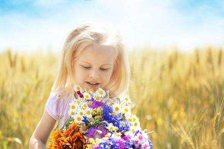 Little girl with bouquet of flowers in the field Banco de Imagens