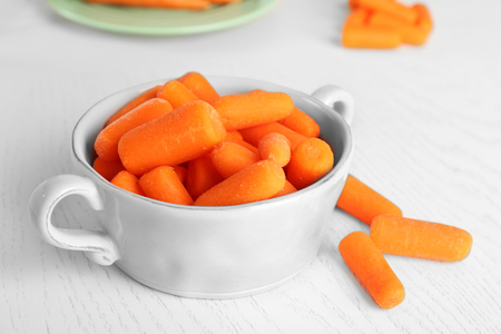 Small baby carrots in bowl on light wooden background