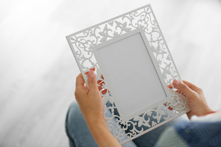 Female hands holding photo frame on light background