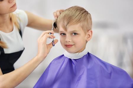 Die Hände des Friseurs machen dem Kind die Frisur Standard-Bild