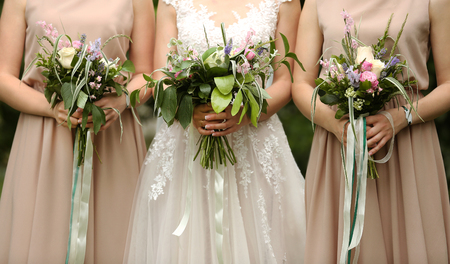 Beautiful bride and bridesmaids holding bouquets