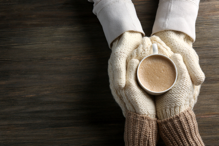 Lovely couple holding cup of coffee in knitted gloves on wooden background