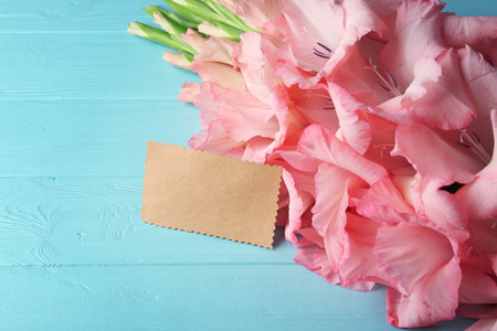 Beautiful gladiolus flowers with card on  wooden background