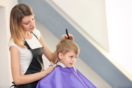 Hairdresser making hairstyle to child on blurred background Stock Photo