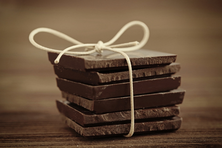 Stack of chocolate pieces on wooden background Archivio Fotografico
