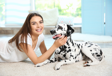 Owner with her dalmatian dog lying on a carpet