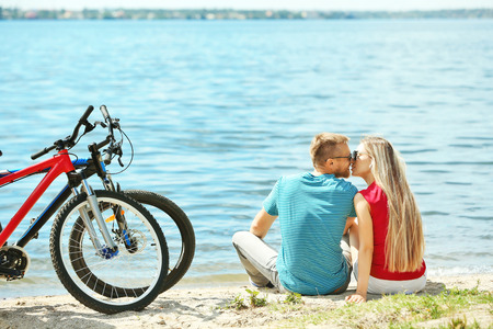 Happy couple with bicycles on the beach Stock Photo