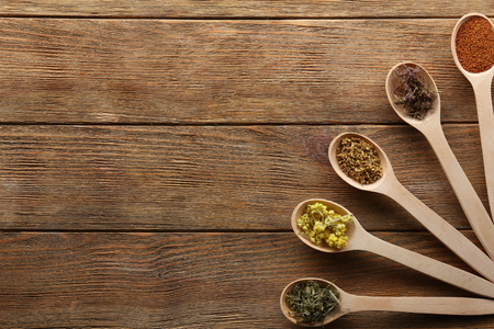 Dried healing herbs and seeds in spoons on wooden background