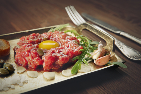 Steak tartar with chopped onion and pickles on a tray Фото со стока