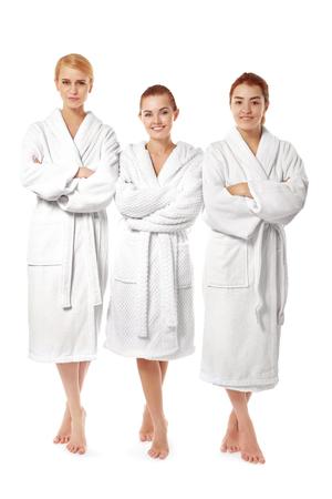 Trois belles femmes en robes de chambre isolés sur blanc