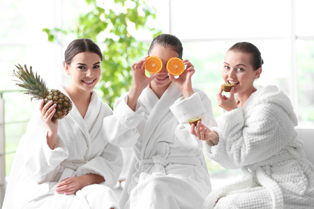 Beautiful girls with fruits in spa salon