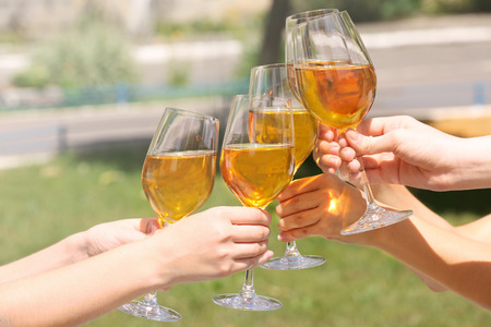 Female hands clinking glasses with white wine outdoors Banque d'images