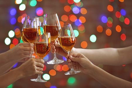 Mani femminili tintinnio bicchieri con vino bianco su sfondo bokeh di fondo