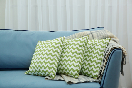 Comfortable sofa with pillows in the room