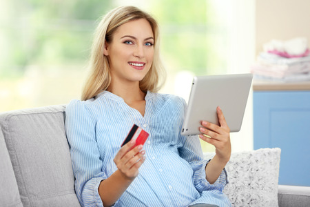 Pregnant woman shopping online on couch Archivio Fotografico