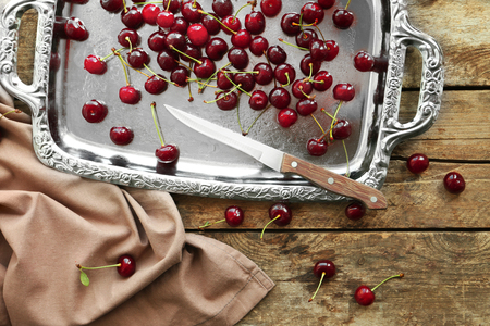 Old metal tray with ripe cherries on wooden background