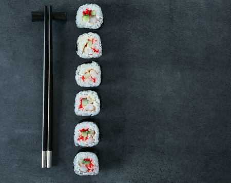 Sushi roll set and chopsticks on dark background