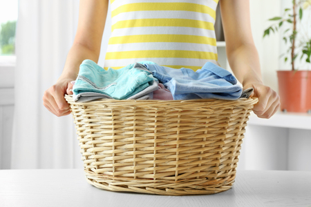 Woman holding wicker basket in laundry Foto de archivo