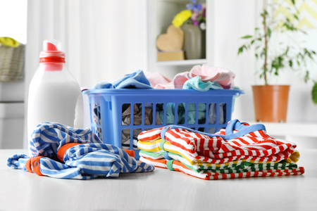 Clothes in plastic basket and detergent