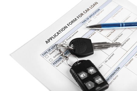 Car key and pen on blank of insurance closeup