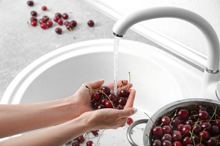 Weibliche Hände, die Haufen von Kirschen waschen Standard-Bild