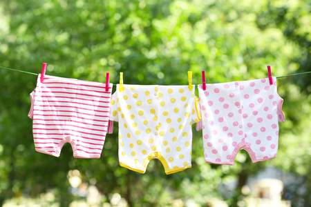 Baby clothes hanging on clothesline Stockfoto