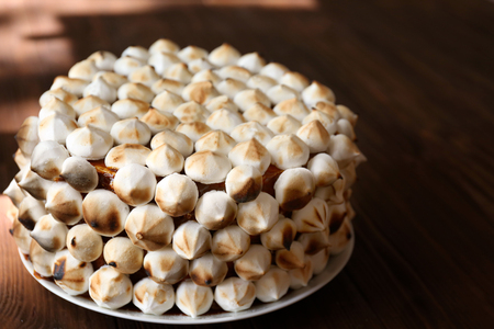 Tasty cake decorated with marshmallow on wooden table