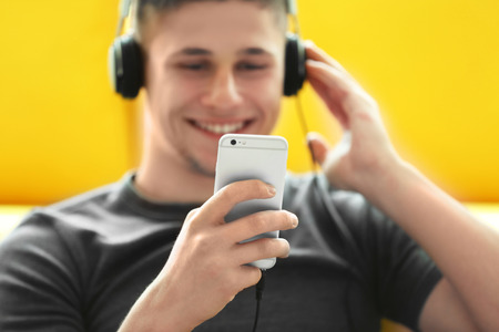 Young man listening to music on smartphone in the room