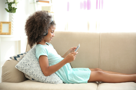 Cute African American girl listening music on couch Stockfoto