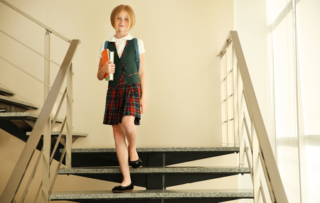Cute schoolgirl with books on staircases