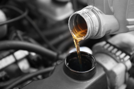 Pouring oil to car engine, close up