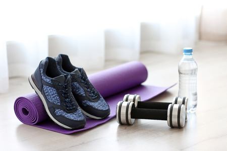 Comfortable sneakers with sport tools on floor Stock Photo