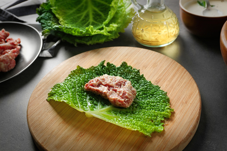 Uncooked cabbage roll on cutting board