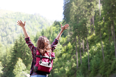 Young woman enjoying the beauty of mountain forest
