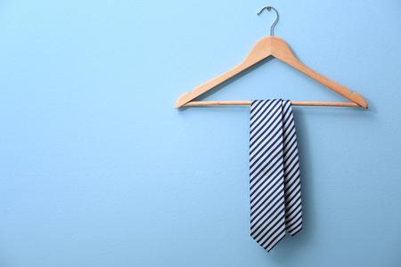 Männliche Krawatte, die auf dem Gestell, blauer Hintergrund hängt