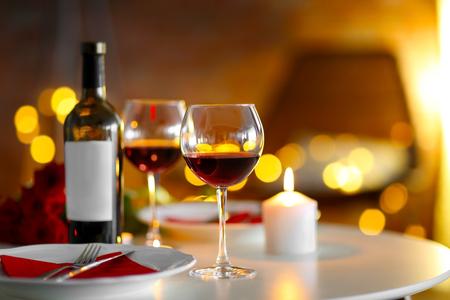 ぼやけた背景にワインとろうそくを持つロマンチックな構成 写真素材 - 107510076