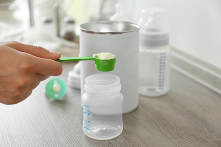 Preparing baby milk formula on wooden table closeup