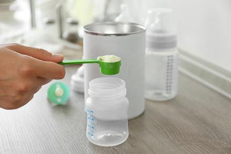 Przygotowanie mleka modyfikowanego dla niemowląt na drewnianym stole zbliżenie