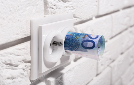 Euro banknotes in socket on white wall