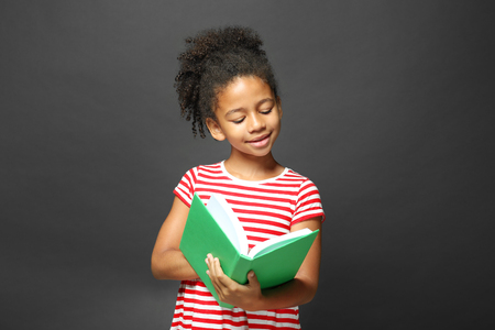 Cute girl reading book on grey background