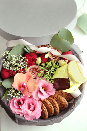 Gift box with flowers and cookies closeup