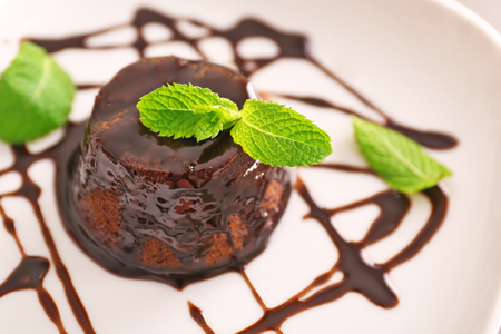 Chocolate fondant cake with mint on the plate, closeup Standard-Bild
