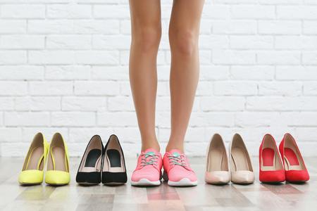 Woman choosing shoes on brick wall background Reklamní fotografie