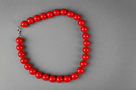 Stylish red beads on grey background