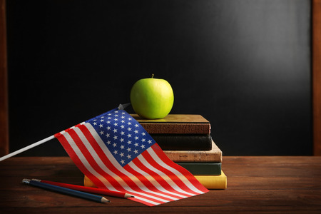 American flag with books and apple on chalk board background