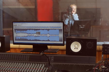 Young woman recording a song in a professional studio. View from sound engineer workplace Stok Fotoğraf