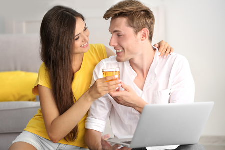 Beautiful couple surfing internet on laptop at home Banco de Imagens
