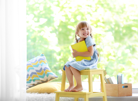 Cute little girl with book sitting on yellow stool Foto de archivo