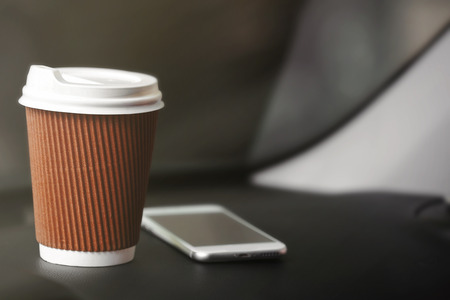 Cup of coffee and smartphone on car console 스톡 콘텐츠