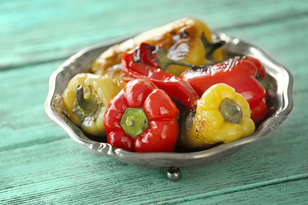 Plate with roasted peppers on wooden background 写真素材